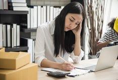 Jovem mulher que senta-se em um escritório domiciliário com seu portátil, fatigante Foto de Stock
