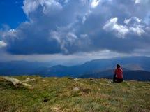 Jovem mulher que senta-se em um penhasco que olha o Mountain View e o céu nebuloso azul Moça que sonha sobre a viagem imagem de stock royalty free
