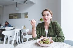 Jovem mulher que senta-se em um restaurante claro acolhedor com uma forquilha em suas mãos, comendo a salada e olhando afastado fotografia de stock