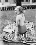 Jovem mulher que senta-se em um terno do sol em um gramado que risca a para trás (todas as pessoas descritas não são umas vivas m imagem de stock royalty free