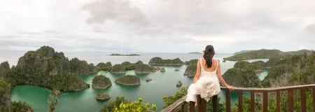 Jovem mulher que senta-se em um terraço que olha o panorama famoso imagens de stock