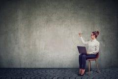 Jovem mulher que senta-se em uma cadeira com escrita do portátil na parede imagens de stock