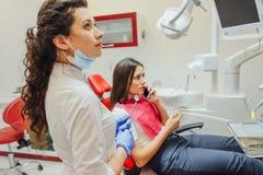 Jovem mulher que senta-se em uma cadeira dental para a nomeação de um doutor Durante este tempo, foi preocupada muito sobre o med fotos de stock royalty free