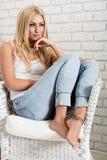 Jovem mulher que senta-se em uma poltrona Humor acolhedor fotografia de stock