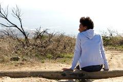 Jovem mulher que senta-se fora em um log Imagem de Stock Royalty Free