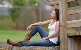 Jovem mulher que senta-se fora no tanque e na sarja de Nimes brancos Fotos de Stock