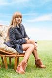 Jovem mulher que senta-se na cadeira Foto de Stock Royalty Free
