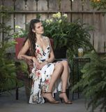 Jovem mulher que senta-se na cadeira de vime no pátio exterior imagens de stock royalty free