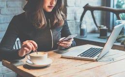 Jovem mulher que senta-se na cafetaria na tabela de madeira, café bebendo e usando o smartphone Na tabela é o portátil