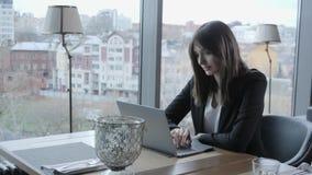Jovem mulher que senta-se na cafetaria na tabela de madeira Na tabela é o portátil de alumínio cinzento Menina que publica em blo video estoque