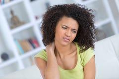 Jovem mulher que senta-se na cama com dor no pescoço fotos de stock