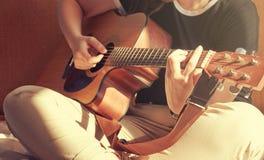 Jovem mulher que senta-se na cama que joga uma guitarra acústica Sunsh foto de stock royalty free