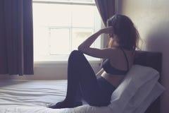 Jovem mulher que senta-se na cama na manhã Imagem de Stock Royalty Free