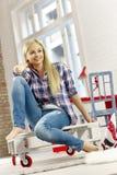 Jovem mulher que senta-se na casa retro Fotos de Stock Royalty Free