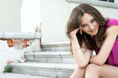 Jovem mulher que senta-se na escada da cidade velha Fotos de Stock Royalty Free