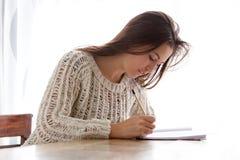 Jovem mulher que senta-se na escrita da tabela no livro Foto de Stock