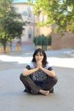 Jovem mulher que senta-se na estrada Foto de Stock