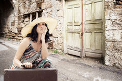 Jovem mulher que senta-se na estrada com mala de viagem Fotos de Stock