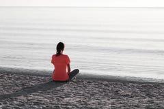 A jovem mulher que senta-se na linha costeira do mar no alvorecer no equipamento atlético, olha para o mar iluminado pelo baixo s imagens de stock