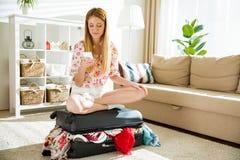 Jovem mulher que senta-se na mala de viagem provida de pessoal com telefone esperto Fotos de Stock