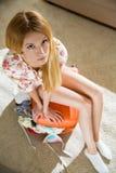 Jovem mulher que senta-se na mala de viagem provida de pessoal com telefone esperto Imagem de Stock Royalty Free