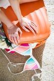 Jovem mulher que senta-se na mala de viagem provida de pessoal com telefone esperto Foto de Stock