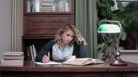 Jovem mulher que senta-se na mesa cansado de trabalhar e de tomar sua cabeça nas mãos filme