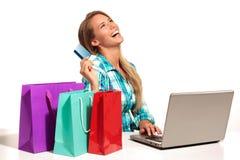 Jovem mulher que senta-se na mesa que compra em linha Fotos de Stock Royalty Free