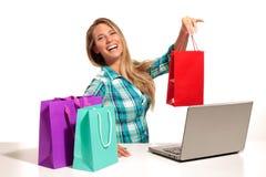 Jovem mulher que senta-se na mesa que compra em linha Fotografia de Stock Royalty Free