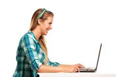 Jovem mulher que senta-se na mesa que compra em linha Fotografia de Stock