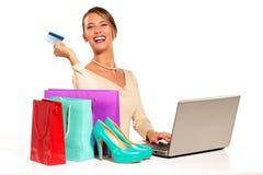 Jovem mulher que senta-se na mesa que compra em linha Imagens de Stock Royalty Free