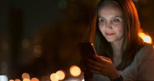 Jovem mulher que senta-se na noite na cidade com smartphone video estoque