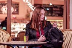 Jovem mulher que senta-se na noite em um café e que olha para enegrecer a trouxa fotografia de stock