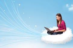 Jovem mulher que senta-se na nuvem com portátil Foto de Stock Royalty Free