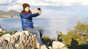 Jovem mulher que senta-se na parte superior da rocha filme