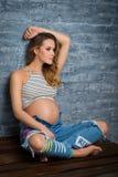 Jovem mulher que senta-se na parte superior e nas calças de brim Conceito pendente louro grávido da paternidade imagem de stock royalty free