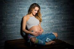 Jovem mulher que senta-se na parte superior e nas calças de brim Conceito pendente louro grávido da paternidade fotos de stock
