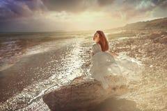 jovem mulher que senta-se na pedra na costa de mar fotos de stock royalty free