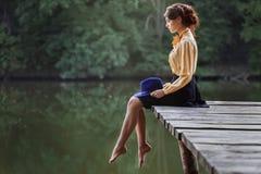 Jovem mulher que senta-se na ponte de madeira Fotos de Stock