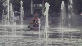 Jovem mulher que senta-se na posição de metade-Lotus dentro da fonte vídeos de arquivo
