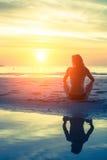 Jovem mulher que senta-se na praia durante o por do sol fotografia de stock royalty free
