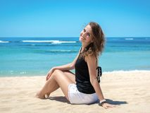 Jovem mulher que senta-se na praia e que relaxa Fotos de Stock Royalty Free