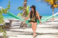 Jovem mulher que senta-se na rede na praia fotos de stock