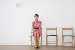 Jovem mulher que senta-se na sala de espera foto de stock