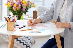 Jovem mulher que senta-se na tabela com imagens da coloração foto de stock royalty free