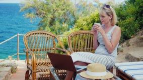 Jovem mulher que senta-se na tabela com um portátil na frente da opinião do mar Freelancer da senhora que trabalha na praia vídeos de arquivo