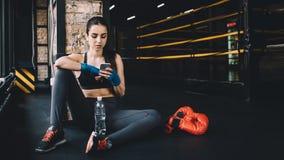 Jovem mulher que senta-se no assoalho após o exercício duro no gym imagens de stock