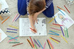 Jovem mulher que senta-se no assoalho com imagens da coloração fotos de stock royalty free