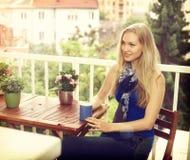 Jovem mulher que senta-se no balcão fotografia de stock royalty free