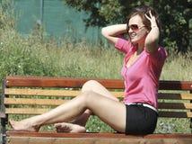 Jovem mulher que senta-se no banco Fotografia de Stock Royalty Free